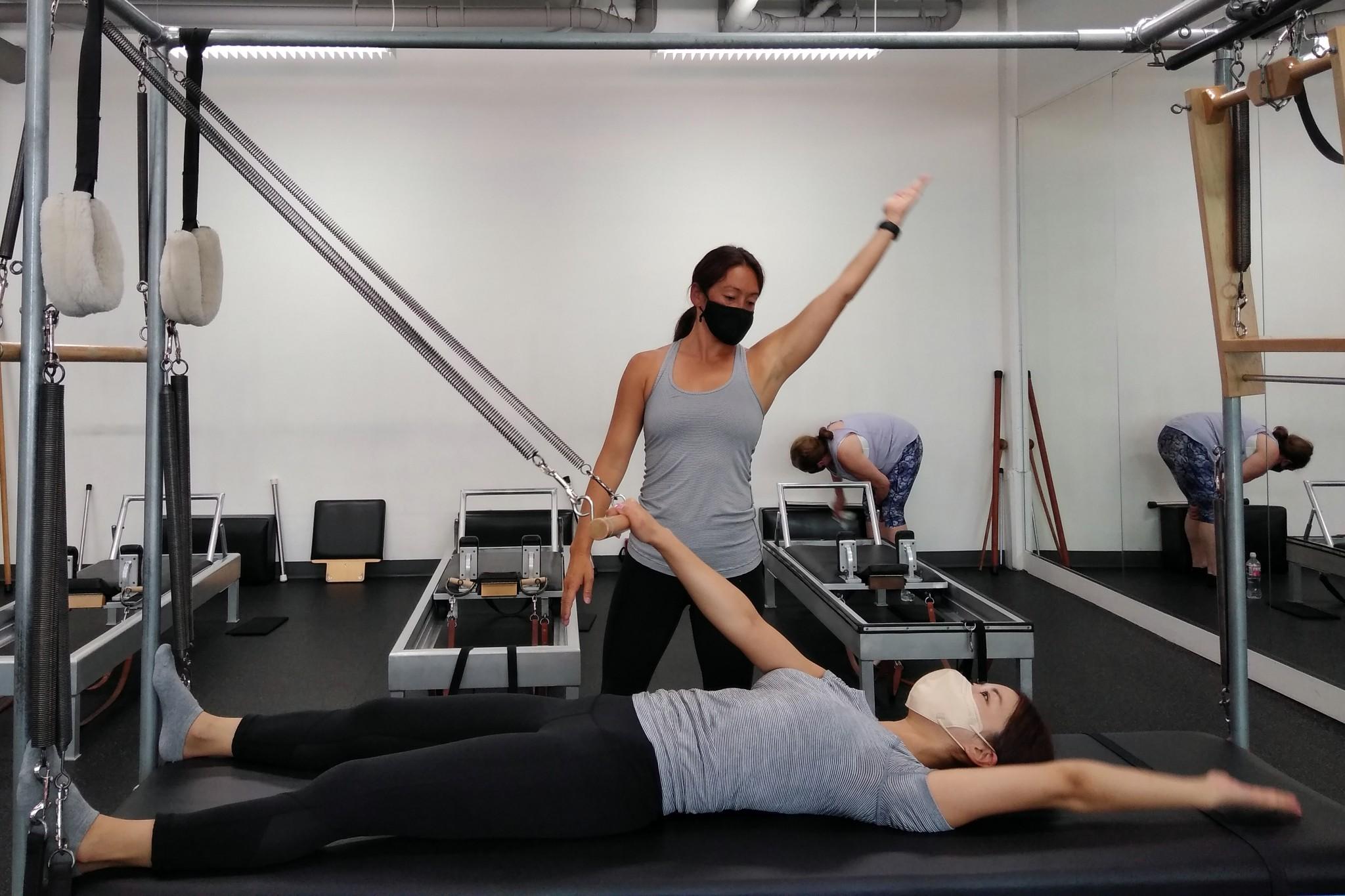Mia teaching Pilates, masked-up