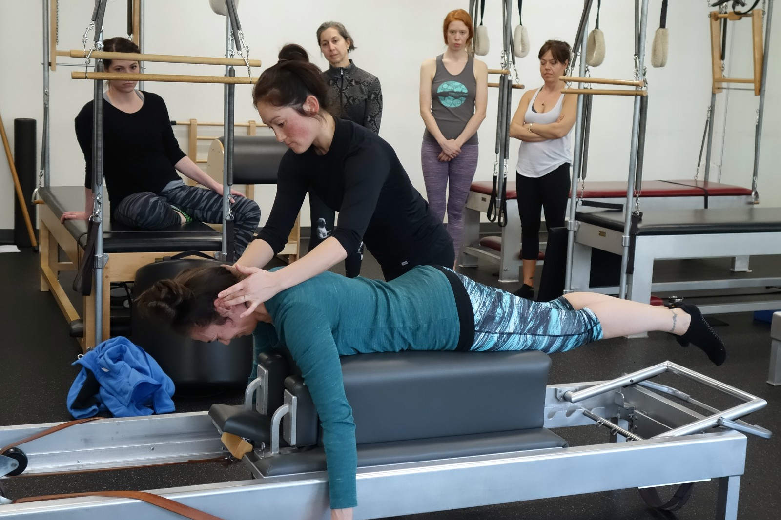 Mia demonstrates Pilates tactile correction